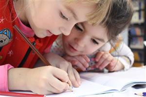 Two kids working together on a paper